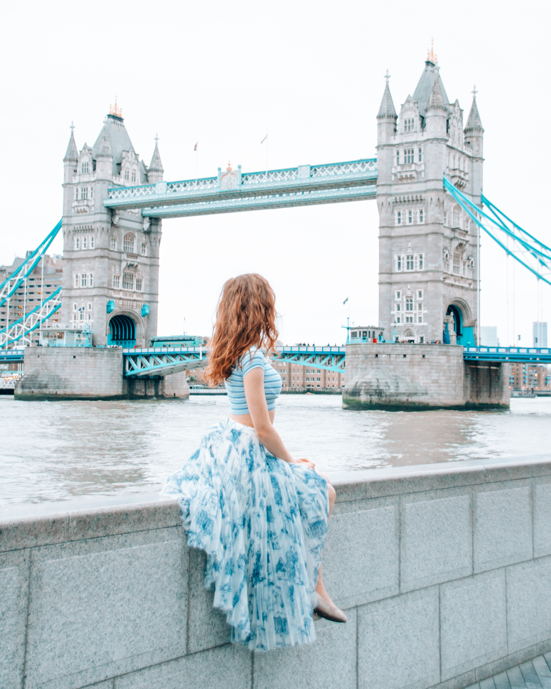 Girl with large skirt looking at Tower Bridge