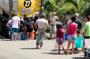 people gathering to obtain water from FEMA after hurricane maria