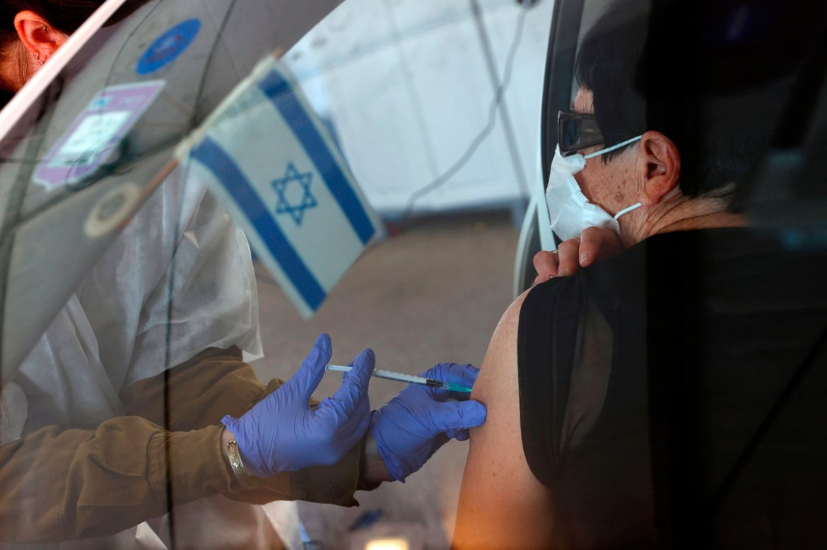 An Israeli senior citizen receives her second Pfizer Covid-19 vaccine at the Maccabi Health Services drive-in vaccination center, in the northern coastal city of Haifa on January 11.