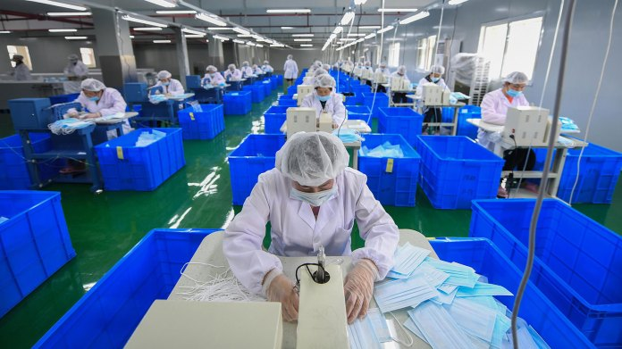 Employees produce face masks on a production line at a Hangzhou Yijia Textile Co., Ltd. workshop in Hangzhou, Zhejiang Province, April 23.