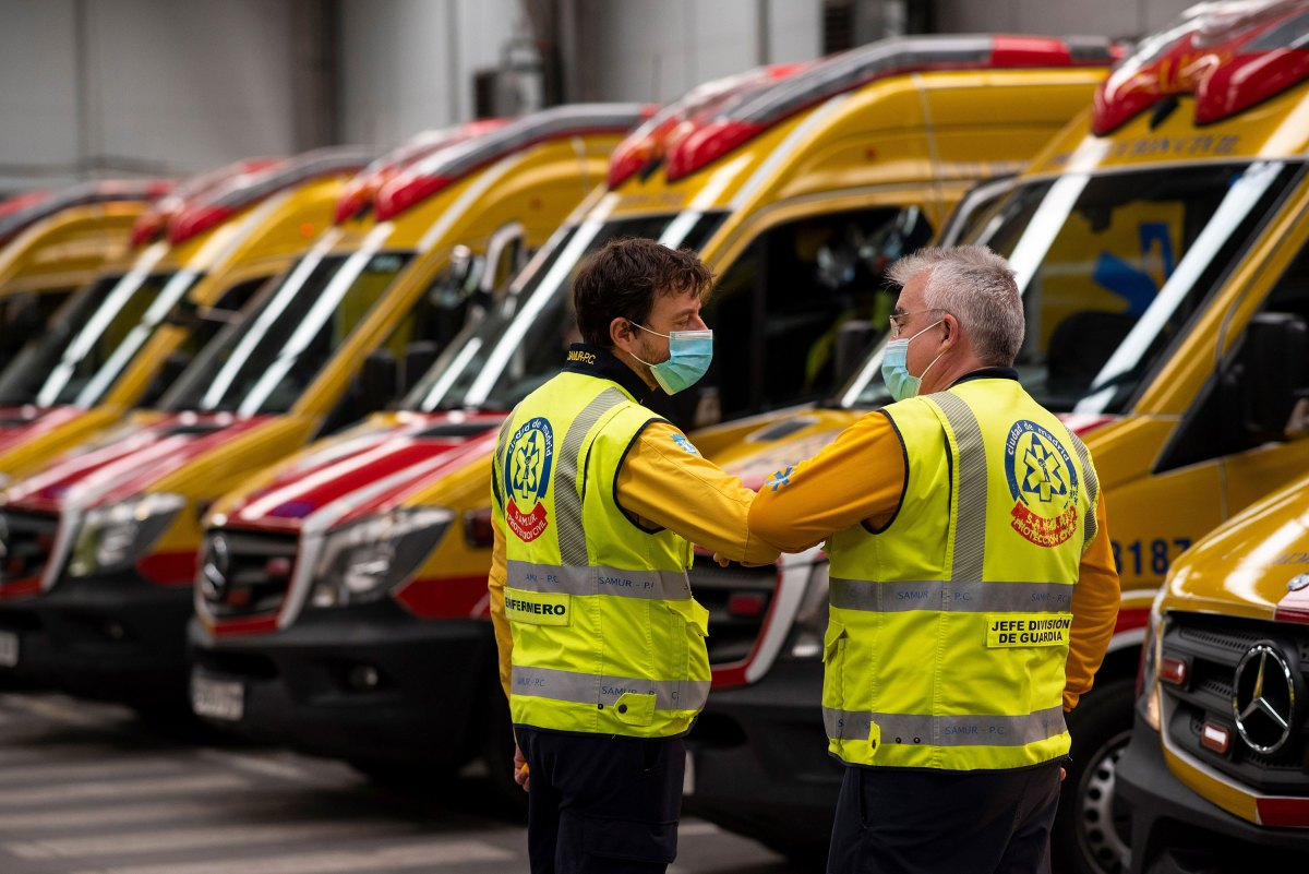 Two members of the Madrid Emergency Medical Service greet each other by touching elbows during a briefing in Madrid on May 15.