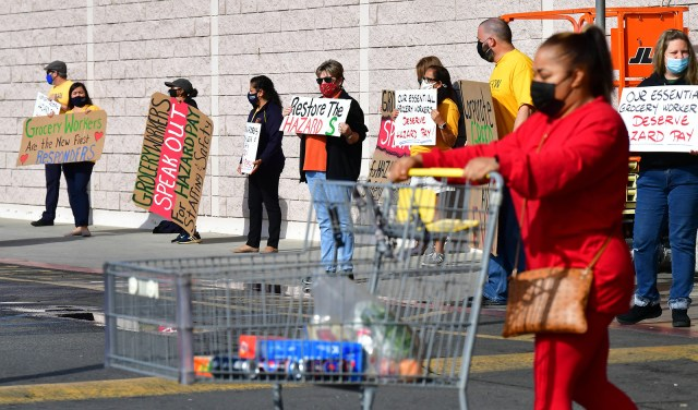 """Workers hold placards in protest at a Food 4 Less supermarket in Long Beach, California on February 3, after a decision by owner Kroger to close two stores rather than pay workers an additional $4 in """"hazard pay"""" for their continued work during the pandemic."""