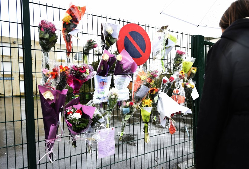 Flowers and letters are placed at the entrance of La Fontaine College in Crepy-en-Valois, France, on Sunday to honor a teacher who died of the coronavirus.