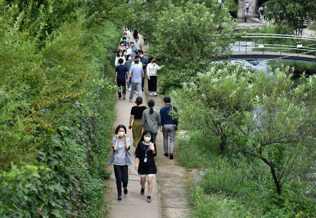 People wearing face masks walk along the Cheonggye stream in Seoul, on September 11, 2020.