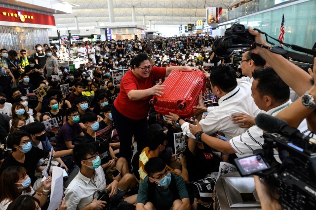 A tourist gives her luggage to security guards as she tries to enter the departures gate during another demonstration by pro-democracy protesters at Hong Kong's international airport on August 13.