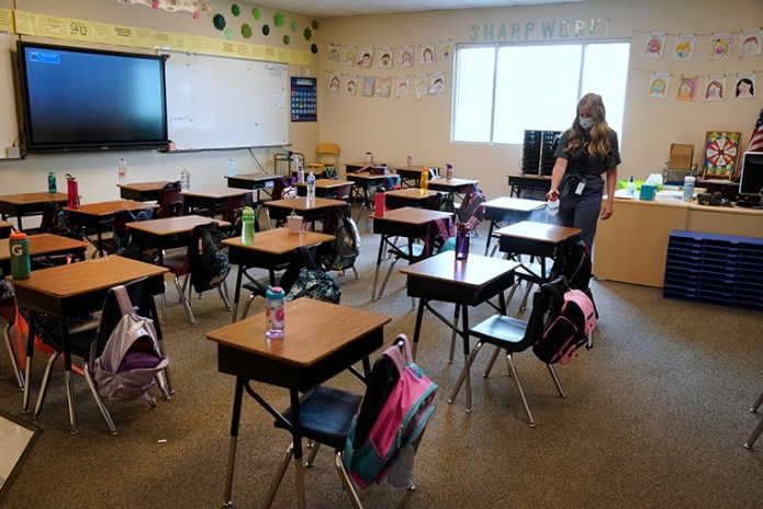 A teacher disinfects desks in a classroom at a public charter school in Provo, Utah, on Thursday, Aug. 20.