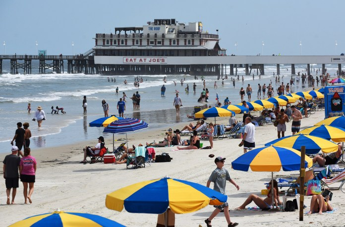People spend time in the sun near the Daytona Beach fishing pier in Florida, on March 24.