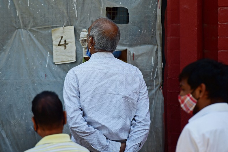 A health official takes a swab sample from a man to test for Covid-19 at a testing centre in Allahabad, India, on April 12.