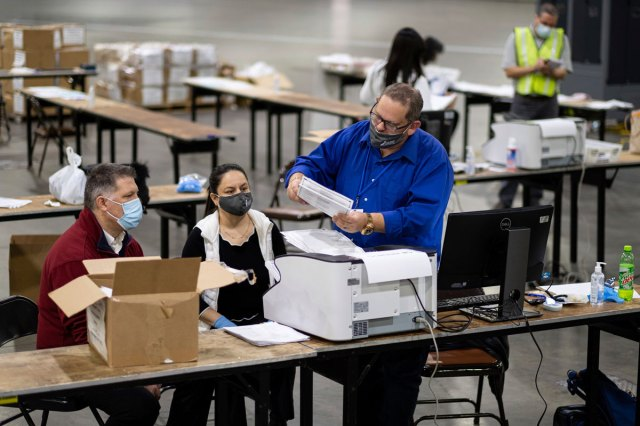 Workers scan ballots as the Fulton County presidential recount gets under way on November 25 at the Georgia World Congress Center in Atlanta.