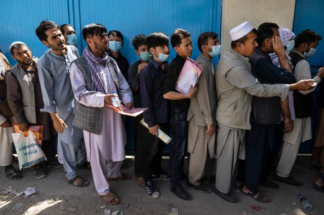 Afghans wait in long lines for hours at the passport office as many are desperate to have their travel documents ready to go in Kabul, Afghanistan on Saturday.