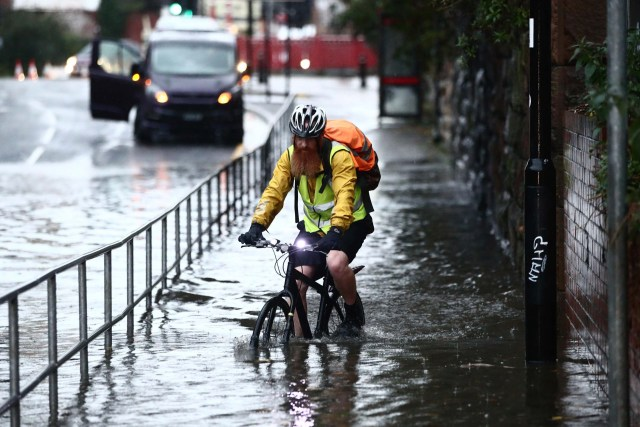 A man cycles through a flooded street in Sheffield, England.