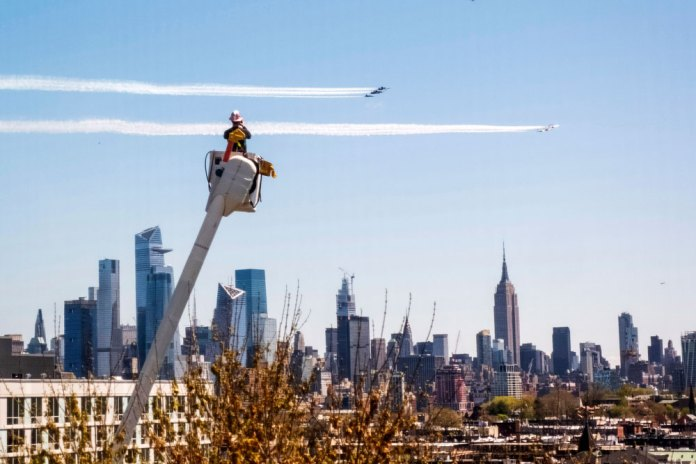 A utility worker watches the U.S. Navy Blue Angels and the U.S. Air Force Thunderbirds