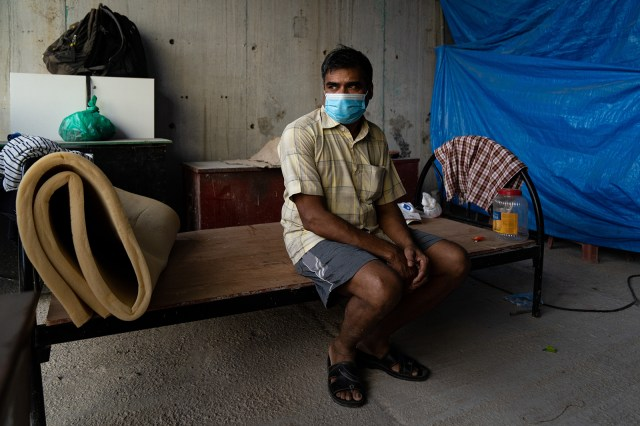 A migrant worker sits on his bed in a construction site on May 17 in Singapore.