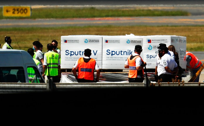 Airport personnel handle containers carrying part of the first batch of 300,000 doses of Sputnik V vaccine from Russia as police officers stand guard at Ministro Pistarini International airport in Ezeiza, Argentina, on December 24.