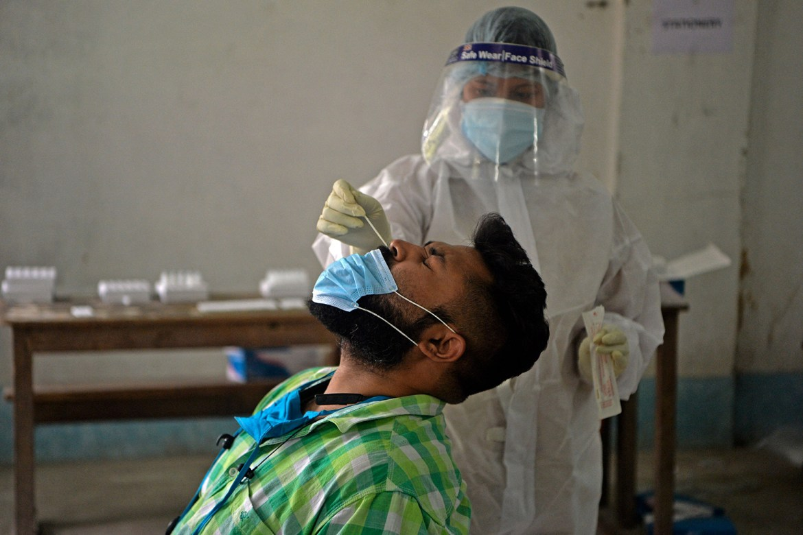 A health worker collects a nasal swab sample at Siliguri college in Siliguri, India, on April 30.
