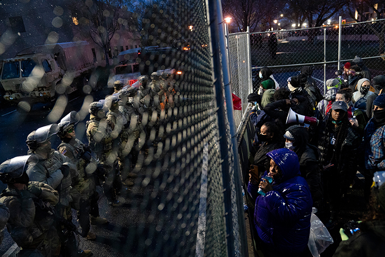 Authorities guard a perimeter fence as demonstrators gather on the other side Tuesday, April 13, 2021, outside the Brooklyn Center (Minn.) Police Department during a protest over Sunday's shooting death of Daunte Wright during a traffic stop.