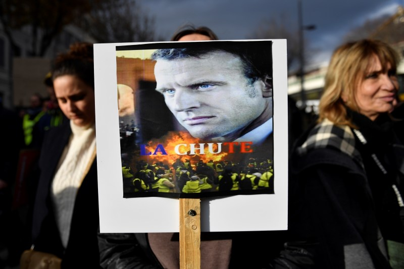 Una donna a Marsiglia tiene un cartello raffigurante la Macron con la parola
