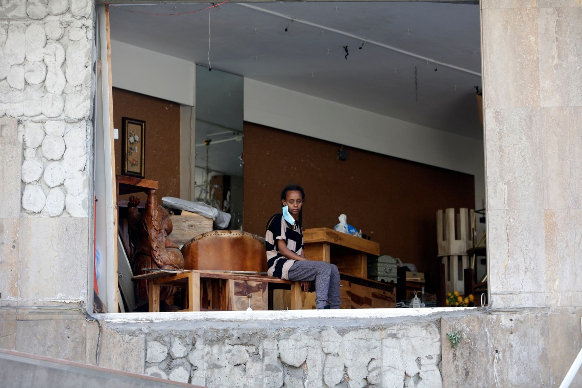 A person looks out of the collapsed facade of an apartment on August 5.