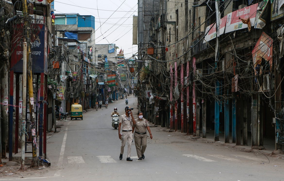 Police officers patrol a street with closed shops during a lockdown in New Delhi on April 20.