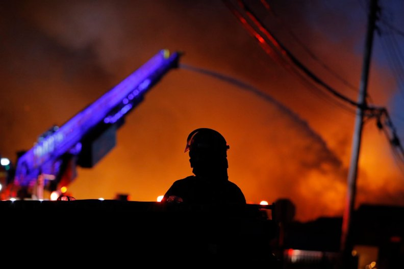 A police watch as firefighters work during demonstrations Thursday, May 28, in St. Paul, Minnesota.