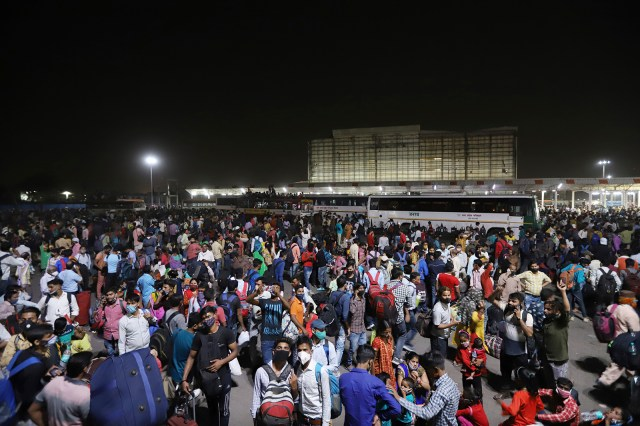 Hundreds of migrant workers in New Delhi wait at a bus station to leave for their villages on Monday.