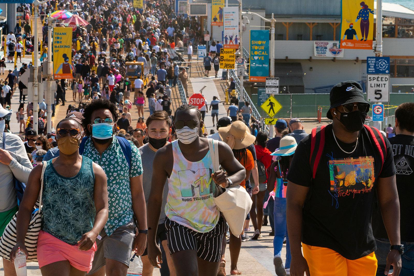 People walk along the Santa Monica Pier in California on Saturday, May 29.