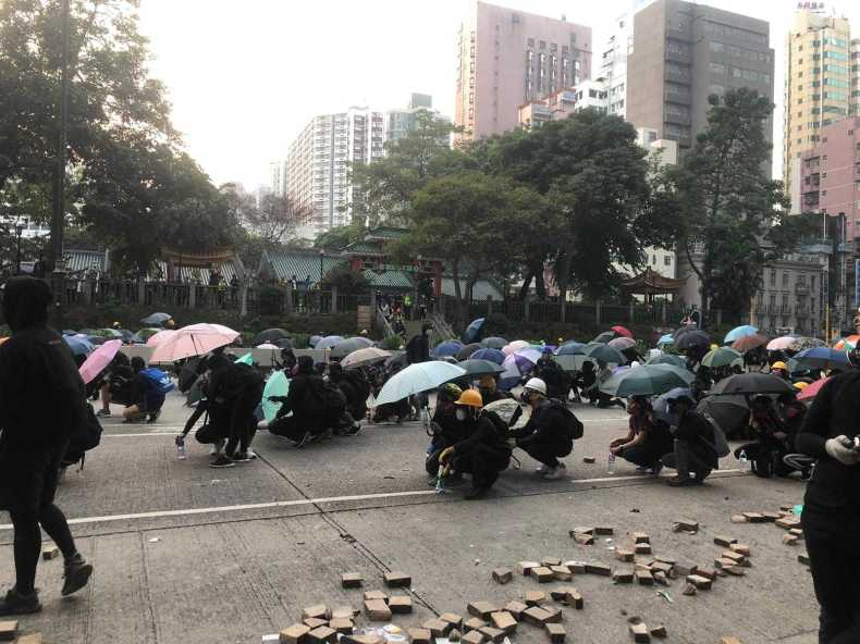 Protesters on Nathan Road, Kowloon, take cover under umbrellas and makeshift shields. Helen Regan/CNN