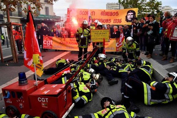 Firefighters lay on the ground as they take part in a demonstration to protest the proposed pension overhauls, in Marseille. Photo: Clement Mahoudeau/AFP via Getty Images