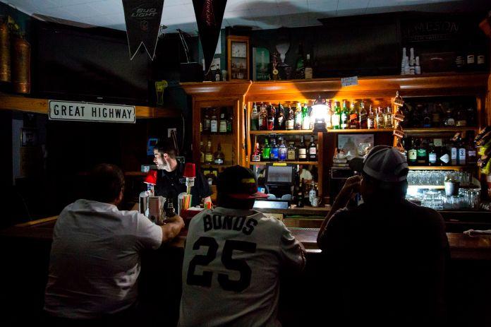 Рик Шоу бармены, используя свет от фонаря во время запланированного отключения электроэнергии.