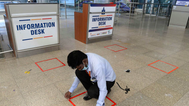 A worker marks squares on the ground at the Rajiv Gandhi International Airport in Hyderabad.
