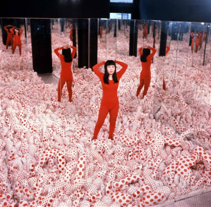 "Kusama pictured inside her work ""Infinity Mirror Room -- Phalli's Field"" in 1965. The floor of the installation was covered with stuffed polka-dot phalluses."