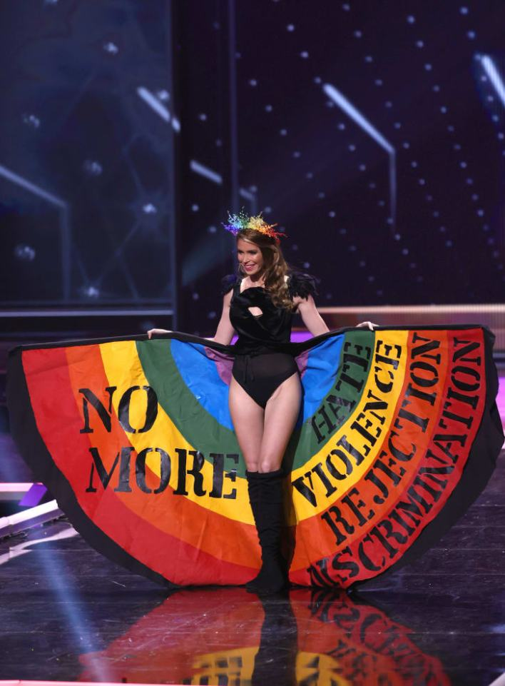 Miss Universe Uruguay Lola de los Santos holds up her rainbow skirt in support of the LGBTQ+ community at Miss Universe 2021.