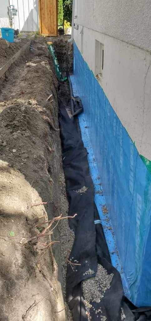 Installing a blue skin on a foundation of a house