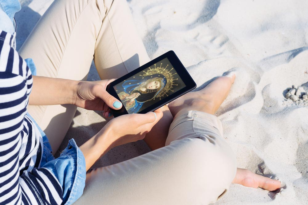 Woman holding tablet on the beach