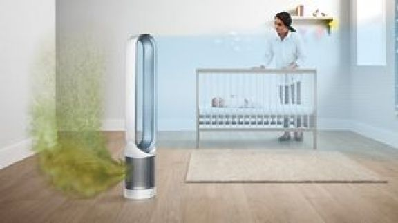 A woman puts a baby in its crib in the background while in the foreground, a Dyson Pure Cool purifier fan is shown sucking green pollutants into its filter and projecting purified air into the room. , Customer Experience and Sales