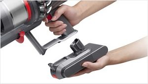Person connects click-in battery to the Dyson V11 Pro vacuum handle