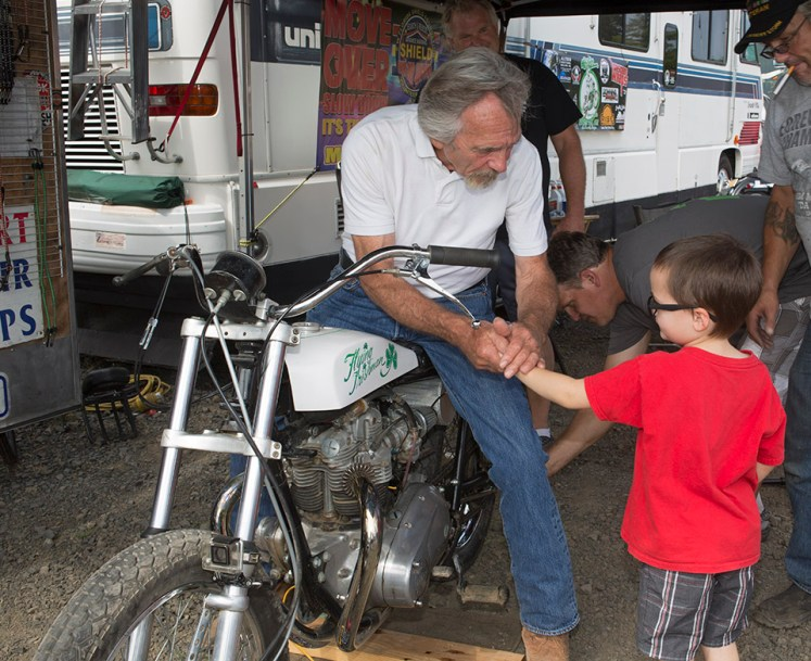 "Denny ""The Flying Irishman"" Edwards, 72, center, shakes hands with Josiah Hill, 5, right, while preparing his 1966 Triumph motorcycle for his first motorcyle jump since retireing 32 years ago. Photographed at the Evergreen Space Museum, in McMinville, Ore, Saturday Aug, 12, 2017."
