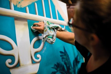 """Eona Skeltor works on a head board that will be used with her panel art called """"Pioneer Inn"""" based on a hotel in Maui, HA. Both pieces will be used in one of McMenamins rooms In Kalama, WA."""