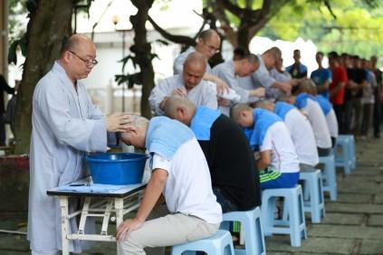 心保和尚與引禮法師一同為男眾信徒剃除鬚髮,成就大眾短期出家因緣。