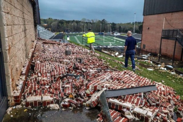 Newnan police officer Donald Evans, left, and principal Chase Puckett walk through the damaged campus of Newnan High School., Friday, March 26, 2022, in Newnan, Ga., the day after a dangerous tornado moved through the area, (John Spink/Atlanta Journal-Constitution via AP)