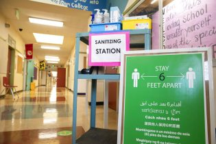 A sanitizing station and sign encouraging social distancing sits in the main hallway during the first day of partial in-person instruction at Garfield Elementary School in Oakland, Calif., Tuesday, March 30, 2021. Garfield Elementary School partially re-opens for students in grades kindergarten through second grade beginning Tuesday. (Jessica Christian/San Francisco Chronicle via AP)