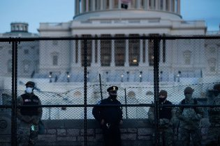 TOPSHOT - A Capitol Police officer stood with members of the National Guard behind a crowd control fence surrounding Capitol Hill on January 7, 2021, in Washington, D.C. (Photo by BRENDAN SMIALOWSKI/AFP via Getty Images)