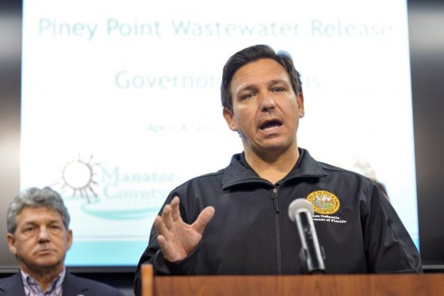 Florida Gov. Ron DeSantis gestures during a news conference Sunday, April 4, 2021, at the Manatee County Emergency Management office in Palmetto, Fla. DeSantis declared a state of emergency Saturday after a leak at a large pond of wastewater threatened to flood roads and burst a system that stores polluted water. (AP Photo/Chris O'Meara)