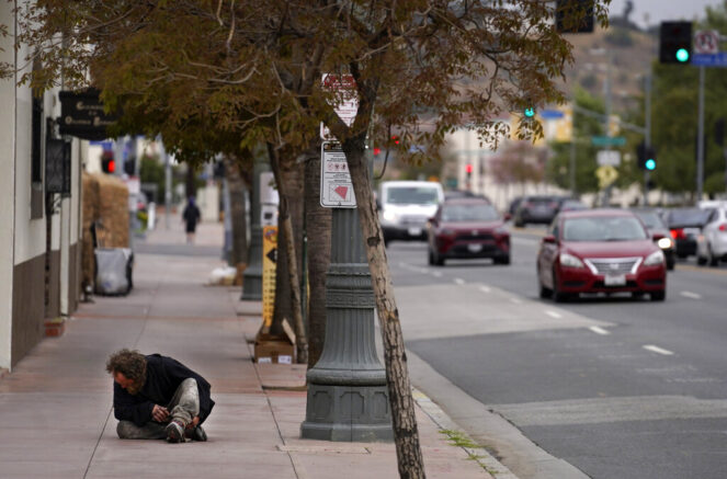 A homeless man sits on the sidewalk on Alameda Street near Union Station, one of the locations for Sunday's 93rd Academy Awards, Wednesday, April 21, 2021, in Los Angeles. (AP Photo/Chris Pizzello)