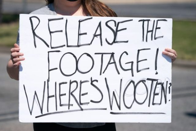 ELIZABETH CITY, NC - APRIL 23: A demonstrator holds a sign addressing Pasquotank County Sheriff Tommy Wooten after an emergency city council meeting April 23, 2021 in Elizabeth City, North Carolina. Protestors were calling for the release of police body camera footage from the shooting death of Andrew Brown Jr. on April 21. (Photo by Sean Rayford/Getty Images)