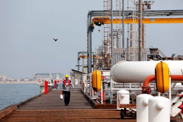 A picture taken on March 12, 2017, shows an Iranian labourer walking the platform of the oil facility in the Khark Island, on the shore of the Gulf. / AFP PHOTO / ATTA KENARE (Photo credit should read ATTA KENARE/AFP via Getty Images)
