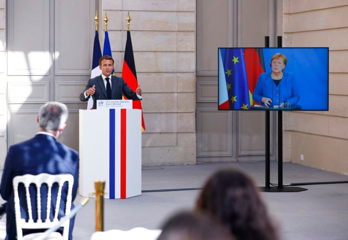 French President Emmanuel Macron gives a joint press conference with Germany's Chancellor Angela Merkel (on the screen) upon the 22nd German-French Ministerial Council videoconference at the Elysee presidential palace in Paris, Monday, May 31, 2021. (Thomas Samson / Pool photo via AP)