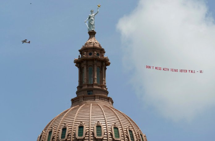A plane pulls the message 'Don't Mess with Texas Voter Y'all' over the Texas Capitol, Tuesday, July 13, 2021, in Austin, Texas. Texas Democrats left the state to block sweeping new election laws, while Republican Gov. Greg Abbott threatened them with arrest the moment they return. (AP Photo/Eric Gay)