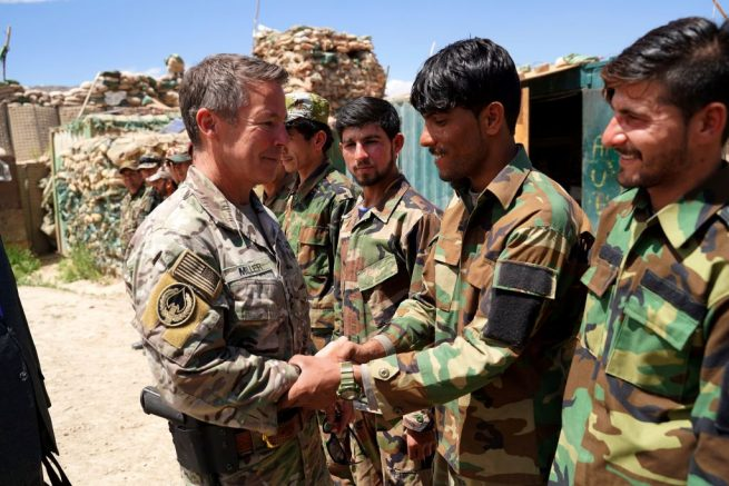 In this photo taken on June 6, 2019, commander of US and NATO forces in Afghanistan General Scott Miller (L) shakes hands with Afghan National Army (ANA) soldiers during a visit at a checkpoint in Nerkh district of Wardak province in west Kabul. - A skinny tangle of razor wire snakes across the entrance to the Afghan army checkpoint, the only obvious barrier separating the soldiers inside from any Taliban fighters that might be nearby. (Photo by THOMAS WATKINS / AFP) / To go with 'AFGHANISTAN-CONFLICT-MILITARY-US,FOCUS' by Thomas WATKINS (Photo credit should read THOMAS WATKINS/AFP via Getty Images)