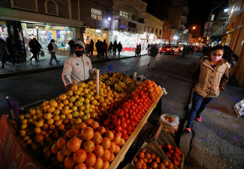 A fruit seller looks on as he waits for customers outside a market in Salta